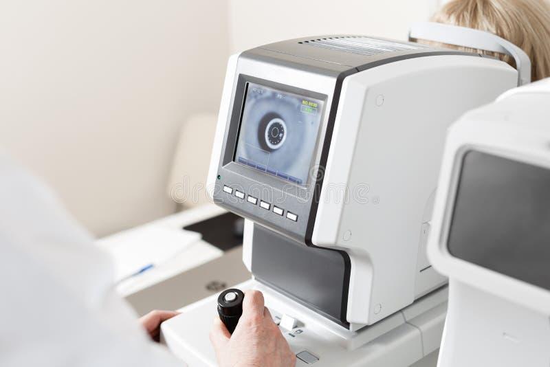 Mulheres que olham a máquina do teste do olho na clínica da oftalmologia imagem de stock royalty free
