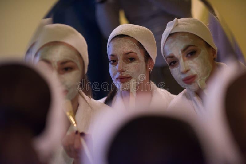 Mulheres que põem máscaraes protetoras no banheiro fotografia de stock