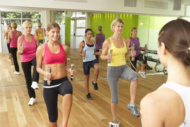 Mulheres que participam na classe da aptidão do Gym que usa pesos imagem de stock