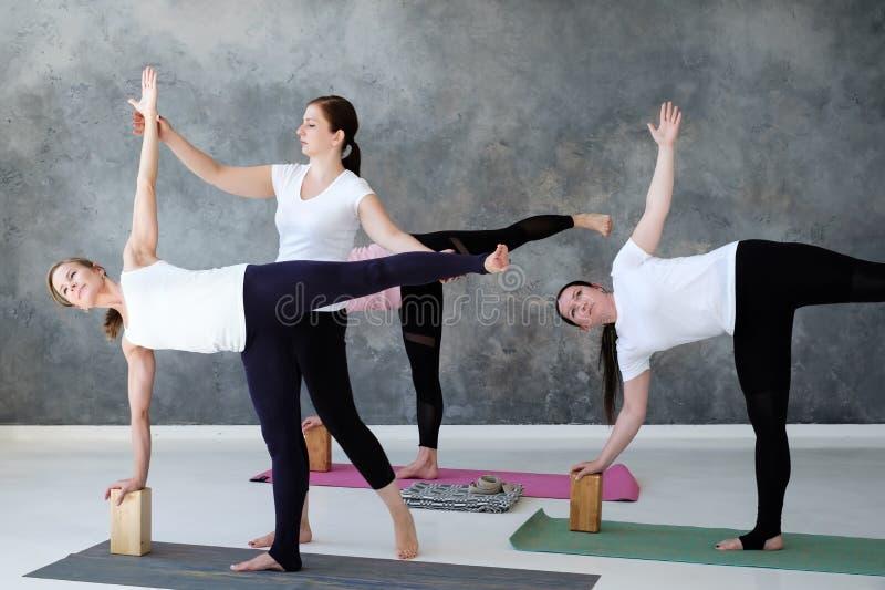 Mulheres que praticam a ioga no exercício da meia lua, pose de Ardha Chandrasana na classe imagens de stock