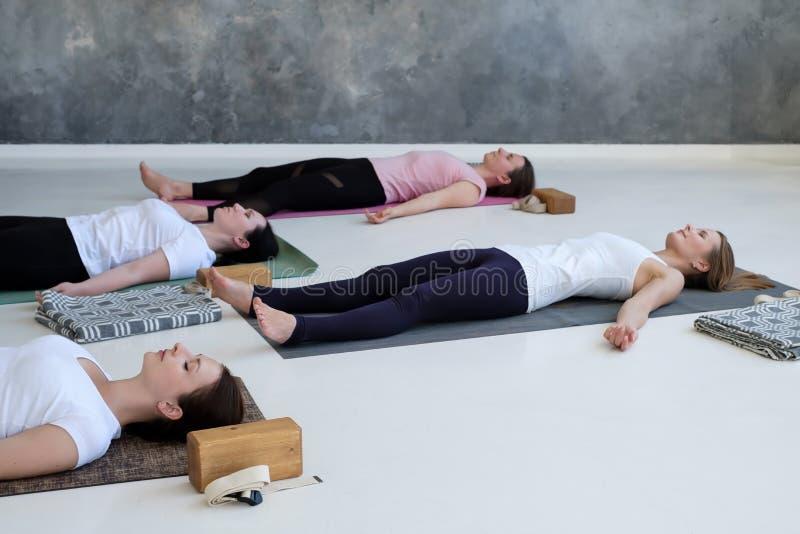 Mulheres que praticam a lição da ioga, fazendo o corpo, Savasana, pose do cadáver do exercício fotografia de stock
