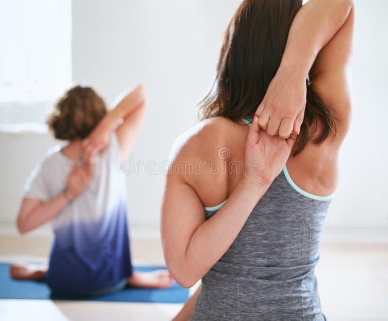 Mulheres que praticam o gomukhasana na classe da ioga imagem de stock royalty free