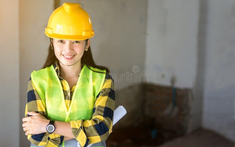 Mulheres que projetam o capacete amarelo vestindo no canteiro de obras imagens de stock