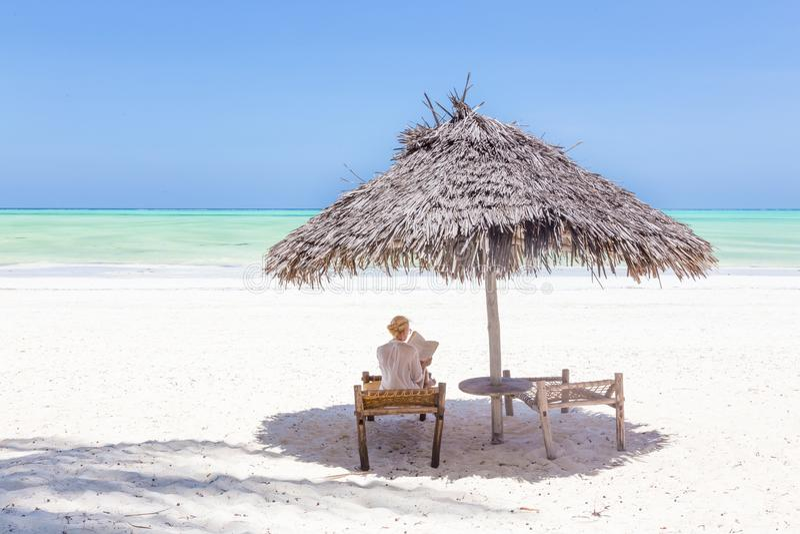 Mulheres que relaxam na cadeira do dack sob o guarda-chuva de madeira na praia tropical foto de stock