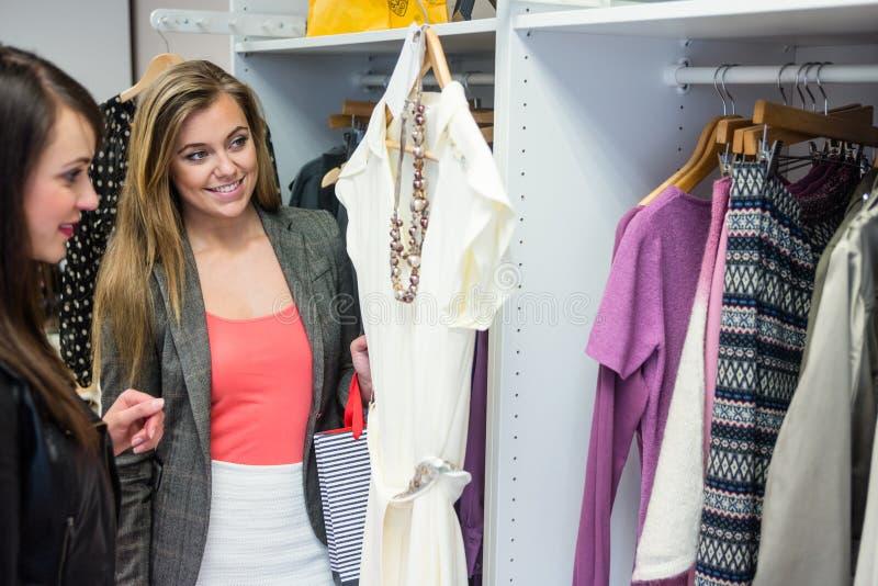 Mulheres que selecionam um vestido ao comprar a roupa fotografia de stock