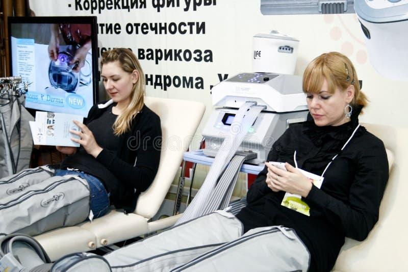Mulheres que sentam-se em uma cadeira da massagem imagens de stock