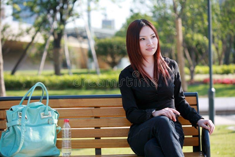 Mulheres que sentam-se na cadeira fora fotografia de stock royalty free