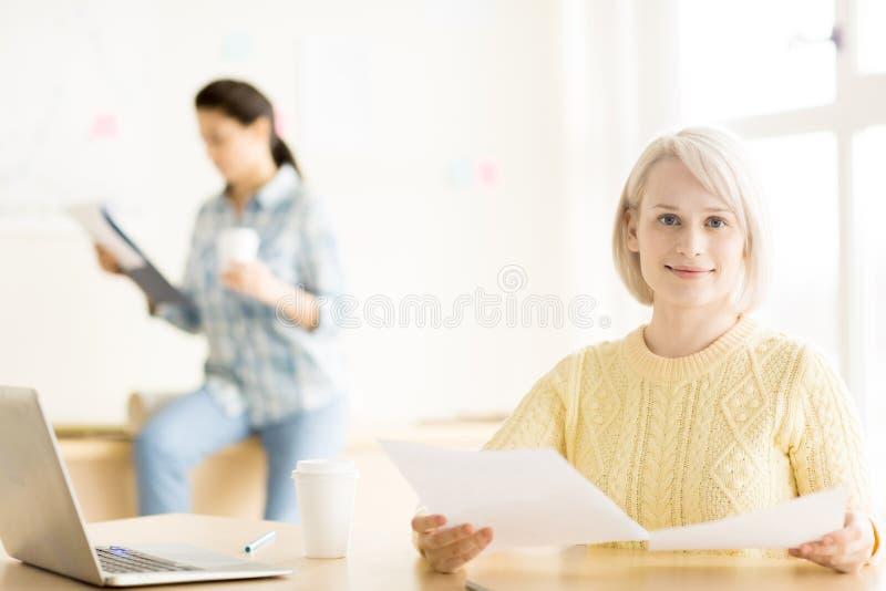 Mulheres que sentam-se no funcionamento do escritório fotos de stock
