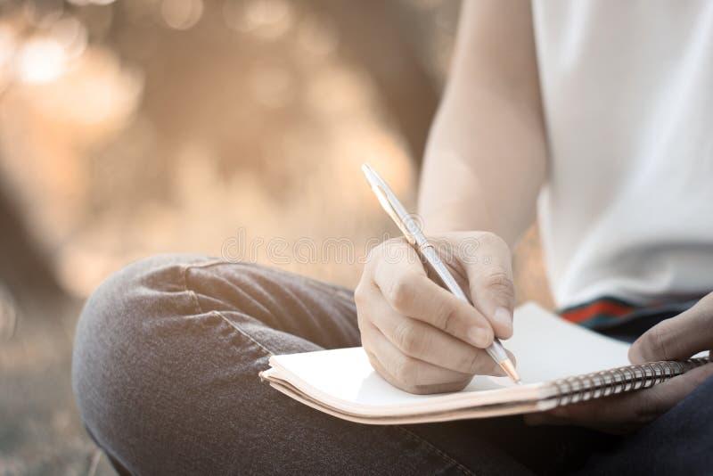 Mulheres que situam e que escrevem a memória no caderno no parque no verão fotos de stock
