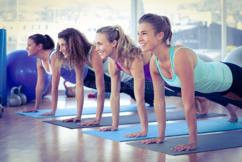 Mulheres que sorriem ao fazer a pose da prancha no fitness center imagem de stock royalty free