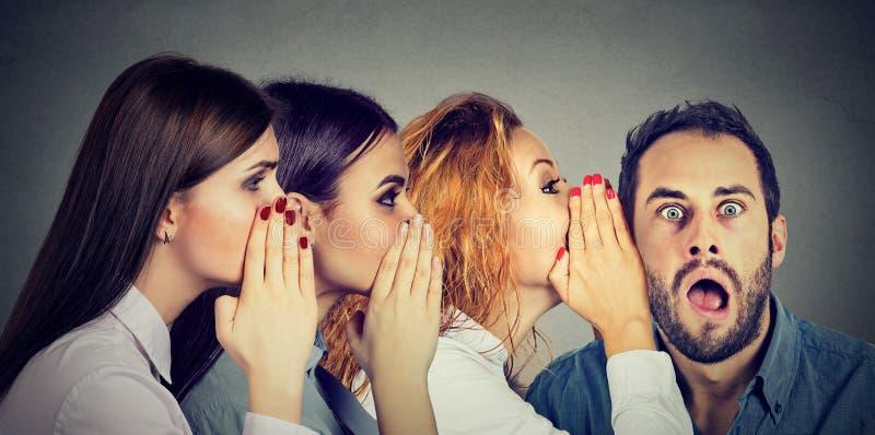 Mulheres que sussurram-se e ao homem surpreendido chocado na orelha imagens de stock