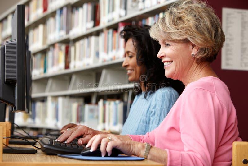Mulheres que trabalham em computadores na biblioteca fotos de stock royalty free