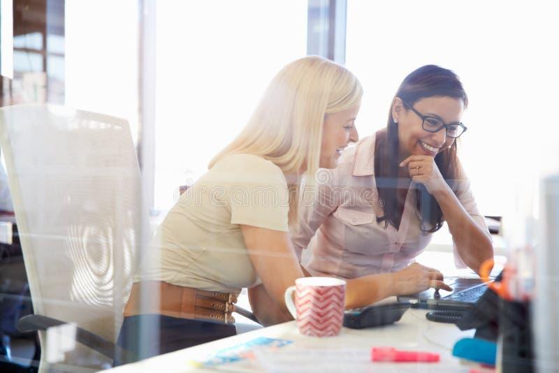 Mulheres que trabalham junto, interior do escritório foto de stock royalty free