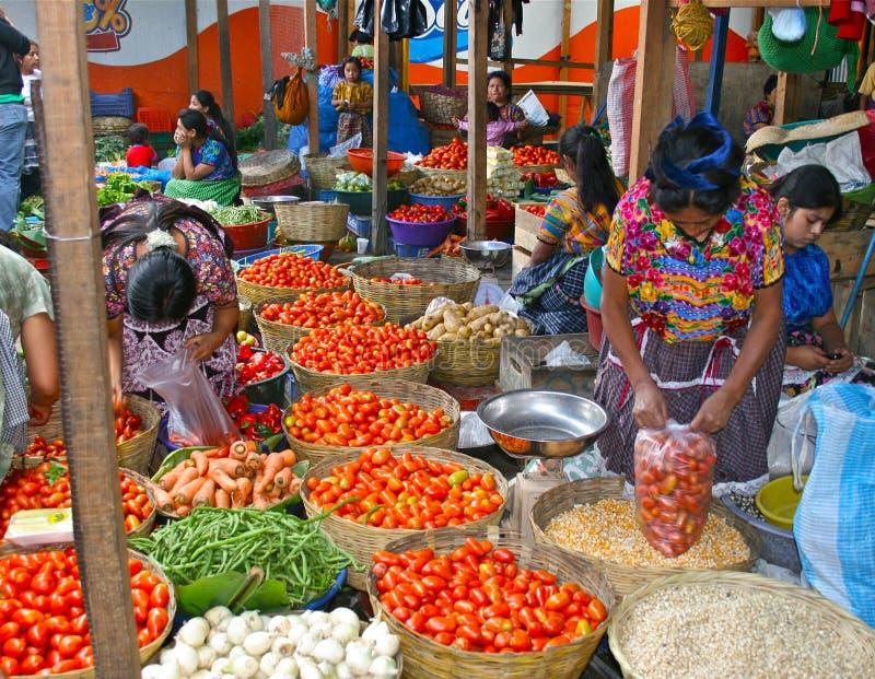 Mulheres que trabalham no mercado colorido de Guatemala foto de stock