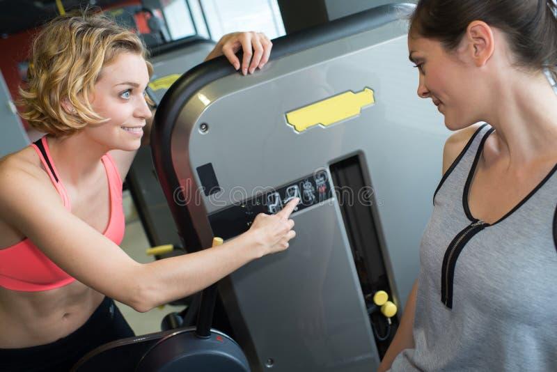 Mulheres que usam máquinas no gym fotografia de stock