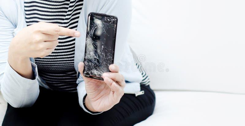 Mulheres que vestem uma camisa azul que guarda um telefone celular quebrado imagens de stock