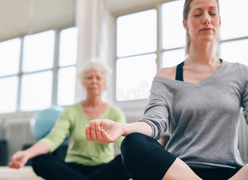 Mulheres relaxado da aptidão que praticam a ioga no gym imagens de stock