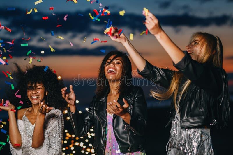 Mulheres a rir a atirar confete ao pôr do sol fotos de stock