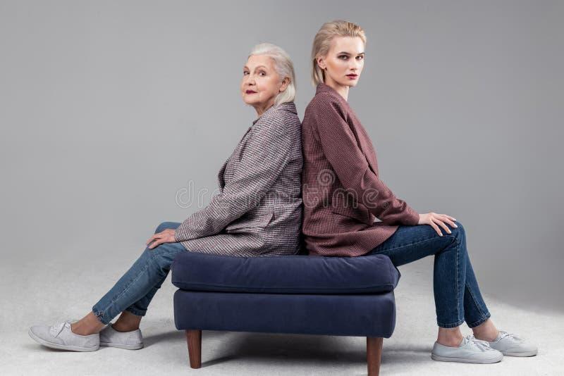 Mulheres sérias resolutos que sentam-se no sofá azul de volta à parte traseira imagens de stock royalty free