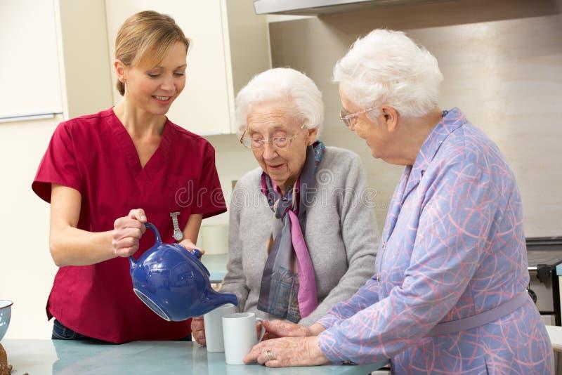 Mulheres sênior em casa com equipa de tratamento fotografia de stock royalty free