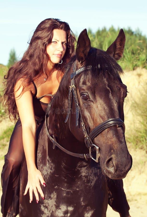 Mulheres sexuais no cavalo preto fotos de stock royalty free