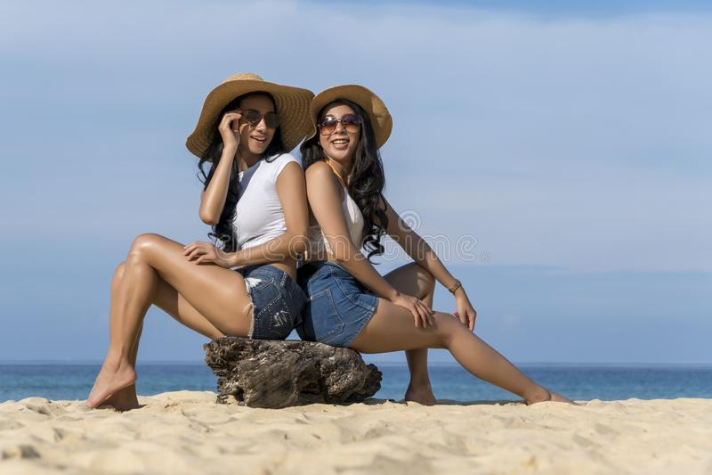 Mulheres 'sexy' asiáticas que sentam-se na praia, curso de férias de verão Conceito do abrandamento e da liberdade imagens de stock