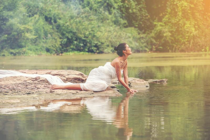 Mulheres 'sexy' bonitas no vestido leve branco que senta-se na rocha Modelo 'sexy' que senta-se ao longo do lago quieto e do luga fotografia de stock