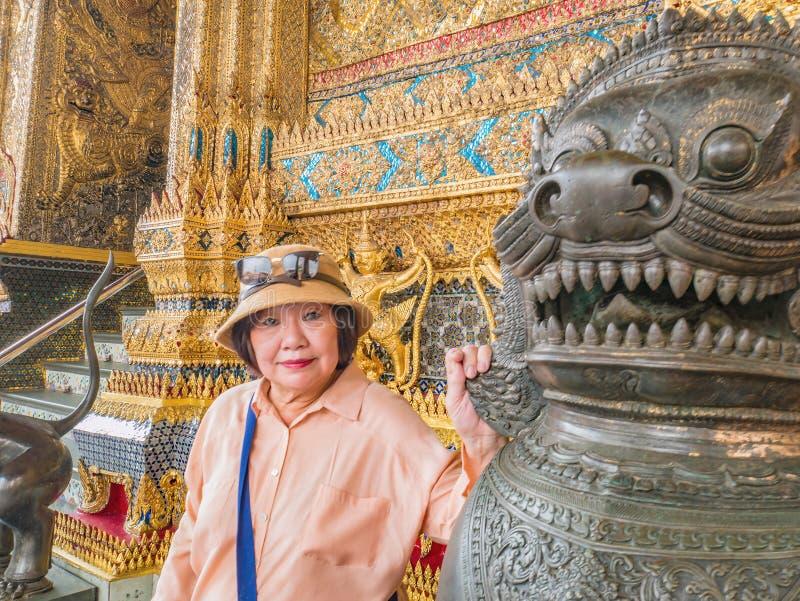 Mulheres superiores da beleza com a estátua tailandesa do leão no templo Banguecoque Tailândia do phrakaew do wat fotos de stock