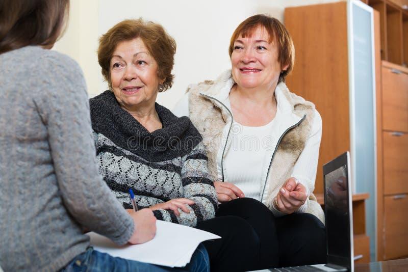 Mulheres superiores que consultam com o agente de operação bancária imagem de stock