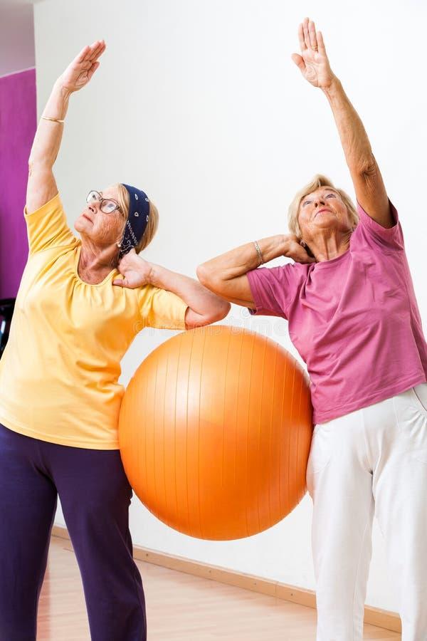 Mulheres superiores que esticam com bola do gym fotografia de stock royalty free
