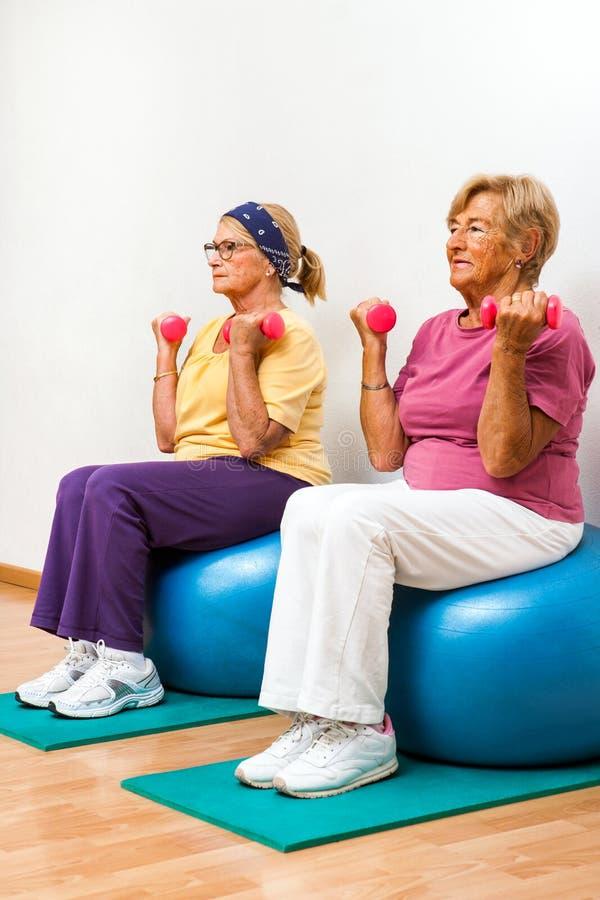 Mulheres superiores que exercitam no gym foto de stock