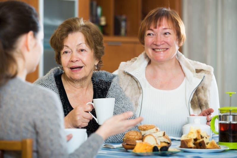 Mulheres superiores que falam com menina quando beber do chá foto de stock royalty free