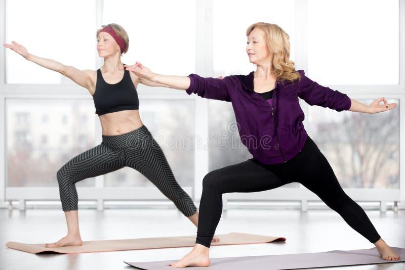 Mulheres superiores que fazem a pose do guerreiro 2 fotos de stock royalty free