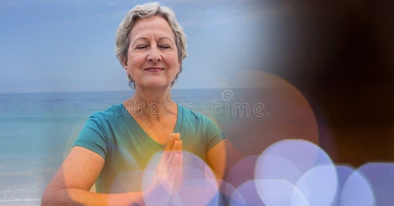 Mulheres superiores que meditam sobre a praia contra o céu fotografia de stock royalty free