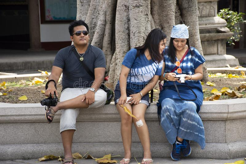 Mulheres tailandesas e homens que sentam-se para relaxar ap?s a visita do curso e deus chin?s rezando do respeito e anjo do viaja imagens de stock royalty free