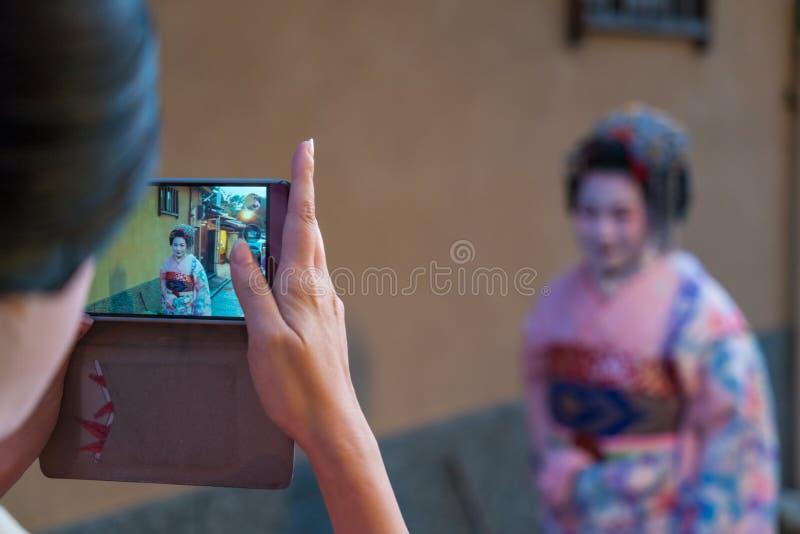 Mulheres vestidas no vestido tradicional da gueixa que est? sendo fotografado no telefone celular fotografia de stock royalty free