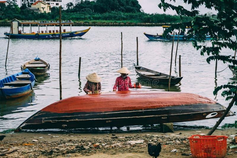 Mulheres vietnamianas que pintam o barco de pesca de A em Hoi An fotos de stock royalty free