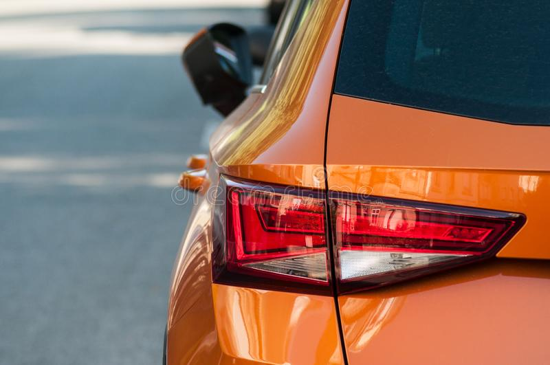 Closeup of rear light of orange Seat leon parked in the street royalty free stock photography