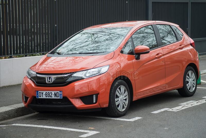 Front view of orange Honda Jazz parked in the street. Mulhouse - France - 22 January 2020 - Front view of orange Honda Jazz parked in the street stock image