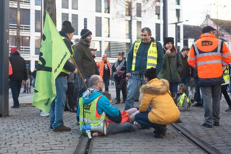 People with yellow vest and flags protesting against the pension reform from the government sitting on railways stock photos