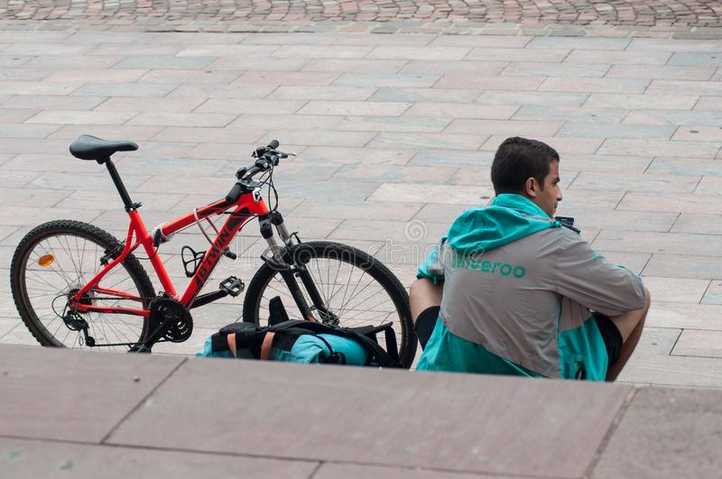 Delivery man from deliveroo british company in mountain bike waiting for delivery to be made sitting on stairs in outdoor royalty free stock photo