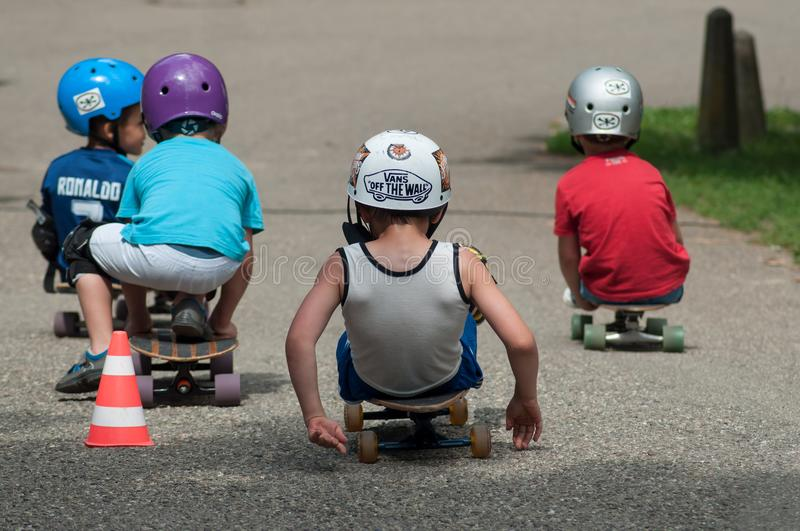 Group of boys sitting on skate board with helmet stock image