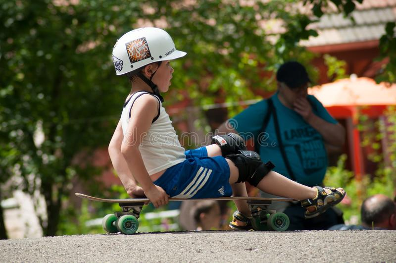 Portrait of boy sitting on skate board with helmet stock photos