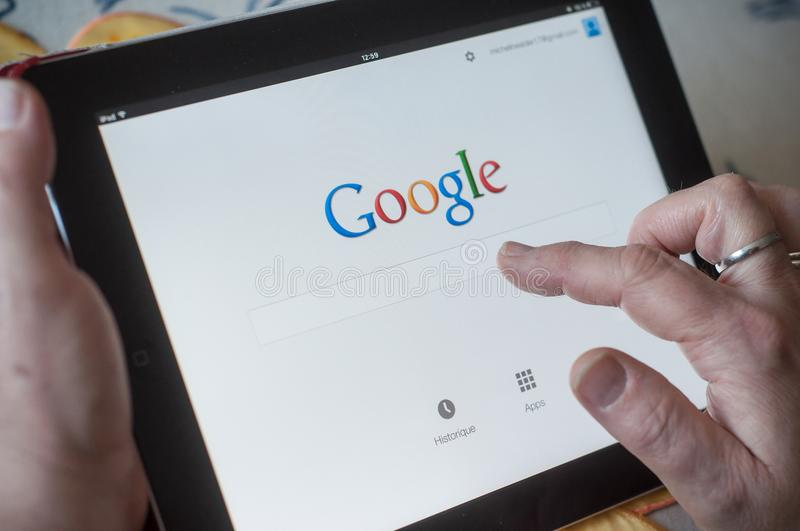 Closeup of woman hands on Google home page search of web site on tablet royalty free stock photography