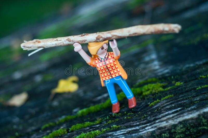 Playmobil figurine carrying a tree trunk above the head on wooden floor stock photos