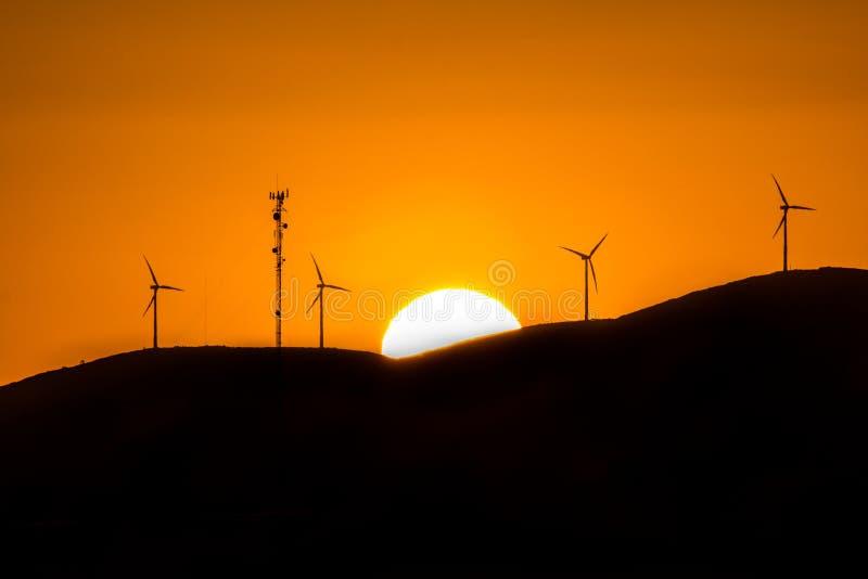 Mulini a vento durante il tramonto sopra le colline fotografia stock libera da diritti