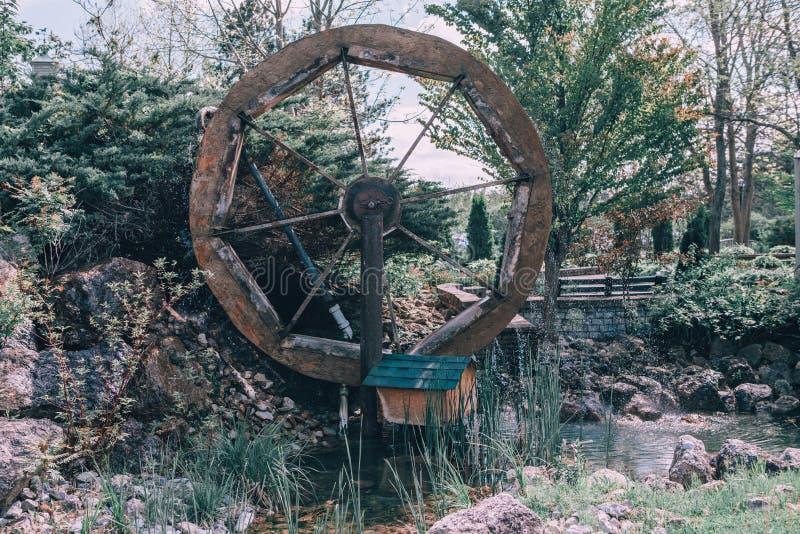 Mulino di legno della ruota dell'acqua vecchio nel villaggio del paese vicino alla corrente dello stagno fotografia stock libera da diritti