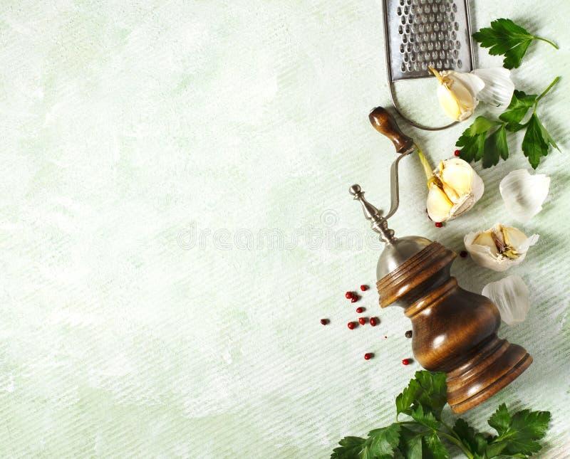 Mulino di pepe d'annata, grattugia, aglio e prezzemolo su fondo leggero fotografie stock