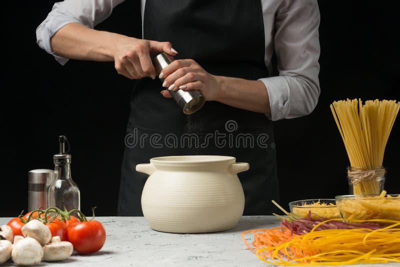 Mulino di pepe nel cuoco unico su un fondo nero Sulle verdure della tavola, spaghetti, pasta, pasta italiana Cottura di concetto fotografie stock libere da diritti