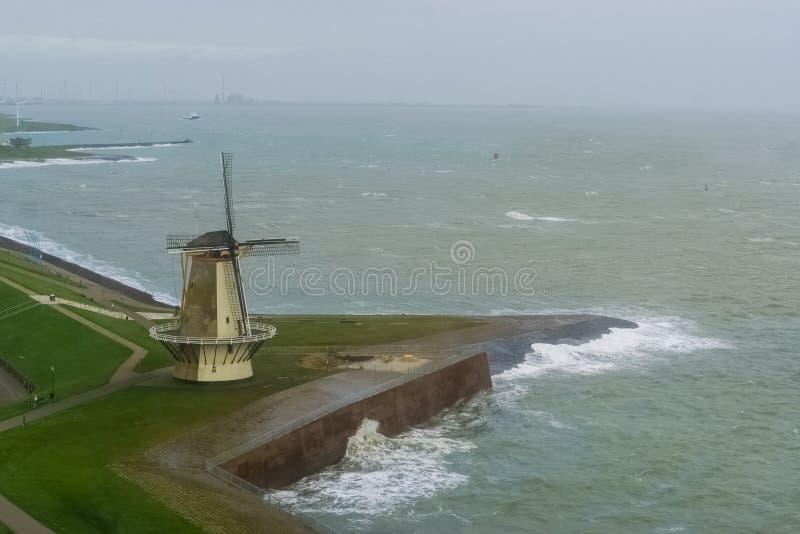 Mulino a vento alla banchina di Vlissingen con il mare selvaggio, città olandese tipica in Zelanda, Paesi Bassi fotografie stock